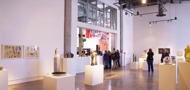 [image description: Interior of an art gallery. Various sculptures stand on white pillars, a few people browsing.]