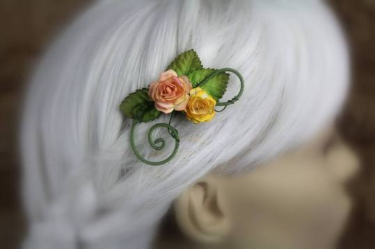 A hair clip made of swirling wire is displayed on a blurred out mannequin head with white hair. The wires are coated in fine green thread and it's decorated with two small roses in coral and dandelion yellow.
