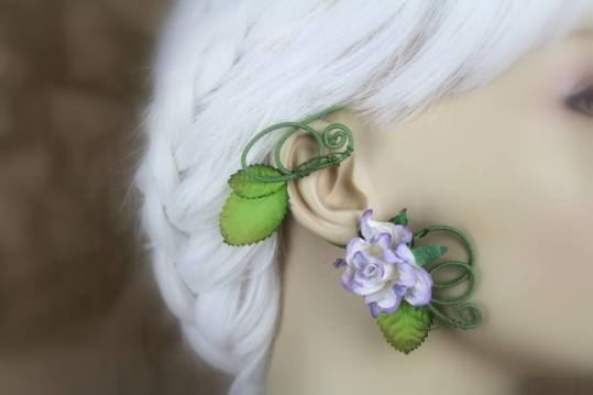 An ear wrap that looks like a flowering vine is displayed on a blurred out mannequin with white hair. The wrap is on green, cotton thread coated wire. There are brown-tipped green leaves and a lavender rose with darker purple tips.