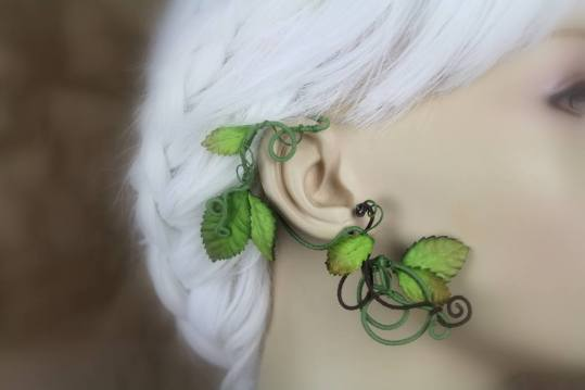 An ear wrap that looks like a flowering vine is displayed on a blurred out mannequin with white hair. The wrap is on green, cotton thread coated wire. There are brown-tipped and solid green leaves and some brown wire accents.