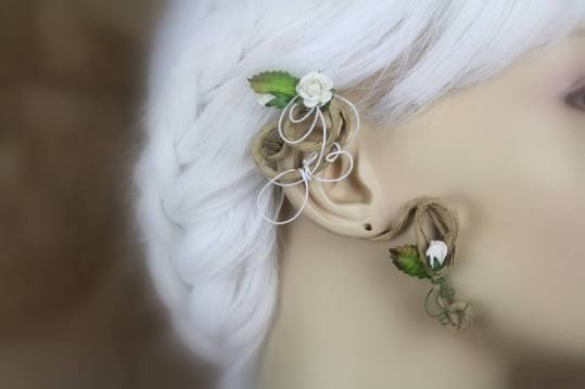An ear wrap that looks like a flowering vine is displayed on a blurred out mannequin with white hair. The wrap is on medium brown, paper coated wire. There are brown-tipped green leaves and tiny snow white roses. There's white wire swirl accents.