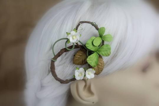 A hair clip made of swirling wire is displayed on a blurred out mannequin head with white hair. The wires are coated in fine green thread and others in natural wood bark. It's decorated with brown leaves, three-leaf clovers, and a few small flowering tree style blossoms.