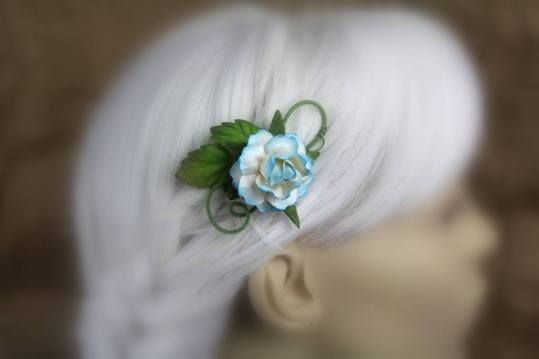A hair clip made of swirling wire is displayed on a blurred out mannequin head with white hair. The wires are coated in fine green thread and it's decorated with a saturated sky blue rose.