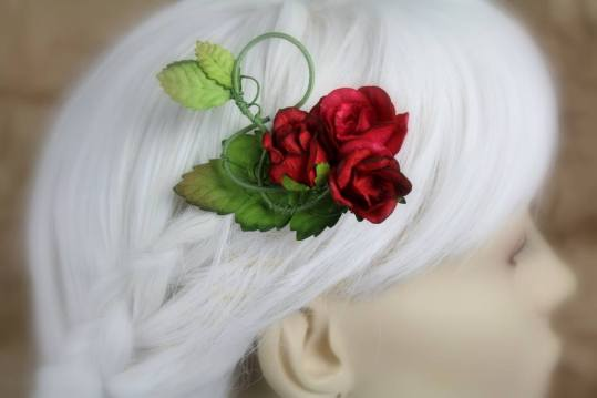 A hair clip made of swirling wire is displayed on a blurred out mannequin head with white hair. The wires are coated in fine green thread and it's decorated with a cluster of three red roses and some bright green leaves with brown ombre tips.