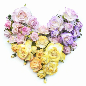 A collection of paper roses in different sizes and petal styles in pinks, yellows, oranges, and purples. They're arranged in the shape of a heart.
