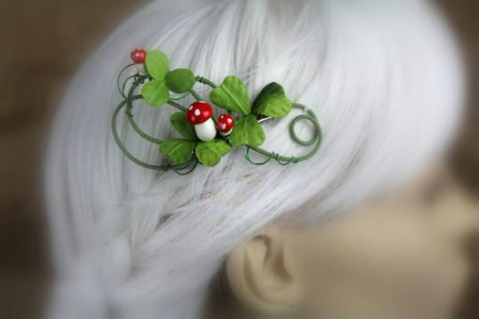 A hair clip made of swirling wire is displayed on a blurred out mannequin head with white hair. The wires are coated in fine green thread and it's decorated with three-leaf clovers and three bright amanita muscaria style mushrooms.