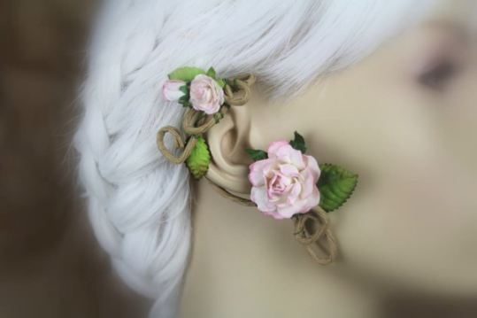 An ear wrap that looks like a flowering vine is displayed on a blurred out mannequin with white hair. The wrap is on medium brown, paper coated wire. There are brown-tipped green leaves and clusters of baby pink roses.