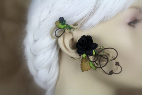An ear wrap that looks like a flowering vine is displayed on a blurred out mannequin with white hair. The wrap is on medium brown, paper coated wire. There are brown and green leaves and a pair of solid black roses.