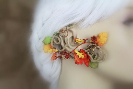 An ear wrap that looks like a flowering vine is displayed on a blurred out mannequin with white hair. The wrap is on medium brown, paper coated wire. There are different kinds of autumn colored leaves, some green, others orange, red, and yellow.