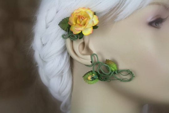 An ear wrap that looks like a flowering vine is displayed on a blurred out mannequin with white hair. The wrap is on green cotton thread coated wire. There are brown-tipped green leaves and a large yellow rose with warm pink-orange tips and a few small matching buds.
