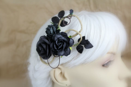 A hair clip made of swirling wire is displayed on a blurred out mannequin head with white hair. The wires are coated in textured brown paper and it's decorated with saturated black roses and small sprays of velvet leaves.