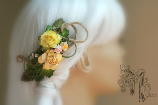 A hair clip made of swirling wire is displayed on a blurred out mannequin head with white hair. The wires are coated in fine green thread and textured brown paper. It's decorated with roses of varying sizes in yellow, orange, and pink.