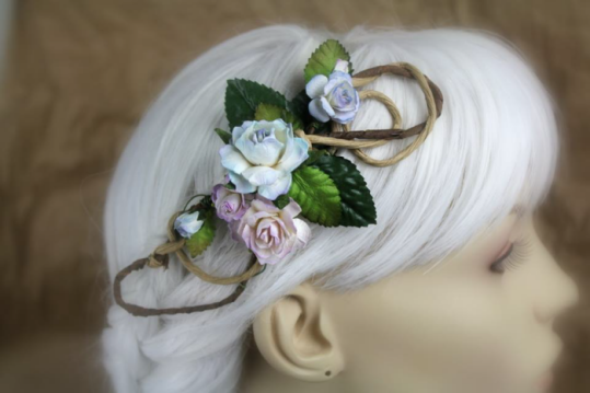 A hair clip made of swirling wire is displayed on a blurred out mannequin head with white hair. The wires are coated in textured brown paper and natural wood fibers. It's decorated with roses in different shades of blue through lavender.