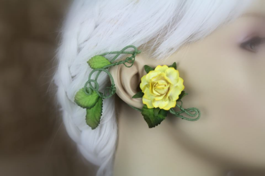 An ear wrap that looks like a flowering vine is displayed on a blurred out mannequin with white hair. The wrap is on a green, cotton thread coated wire. There are green leaves and a large cool toned yellow rose.