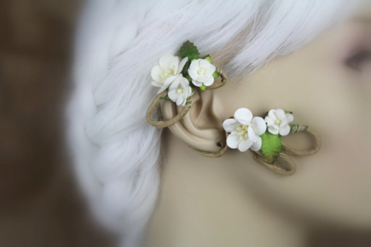 An ear wrap that looks like a flowering vine is displayed on a blurred out mannequin with white hair. The wrap is on medium brown, paper coated wire. There are brown-tipped green leaves and clusters of white flowering tree style blossoms with yellow centers.