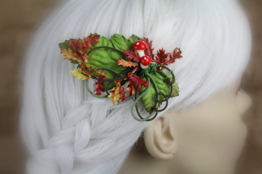 A hair clip made of swirling wire is displayed on a blurred out mannequin head with white hair. The wires are coated in fine green thread, others in brown thread, and it's decorated with a spray of autumn orange and yellow leaves and amanita muscaria mushrooms. Large green leaves in the back provide contrast.