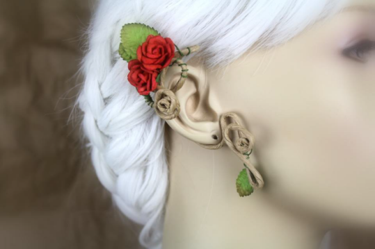An ear wrap displayed on a blurred out mannequin with white hair. The wrap is on medium brown, paper coated wire. There are brown-tipped and solid green leaves and a cluster of bright red roses.
