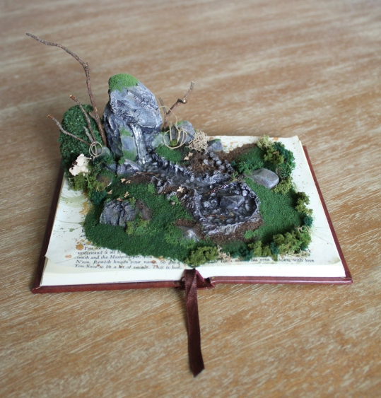 A 3D natural scene is constructed on the open pages of a small hardback book. It appears to be mossy rocks, low grasses, and foliage with a small creek and pond.
