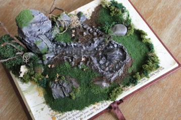 A top view of the piece. A natural scene with stones and foliage appears to grow from the pages of the book.