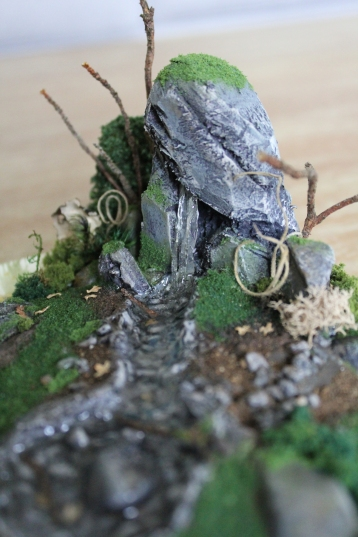 A closeup of the piece's features. A mossy rock is split and faux water pours from it into a small stream. The rock is flanked by small twigs and paper bushes.
