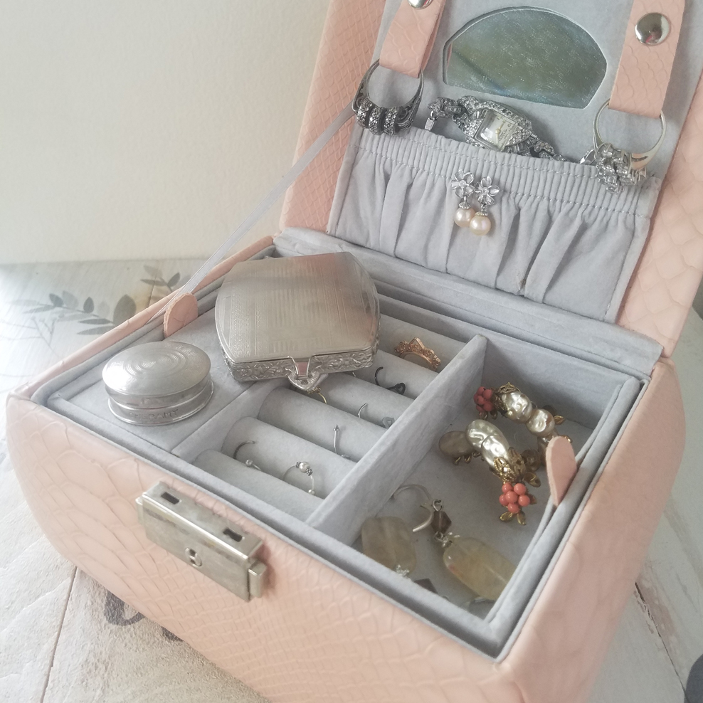 The interior of a jewelry box. There are pieces of new and vintage jewelry inside. Two silver-colored metal vintage makeup compacts are set next to one another in the jewelry box tray. One is quite small and round, the other rectangular with soft edges. Both have detailed engraving for decoration.